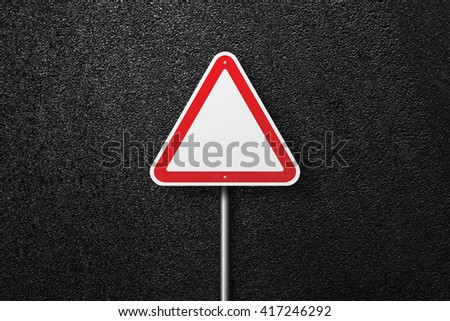 Road signs of the triangular shape. Behind the signs one can see a smooth asphalt road. The texture of the tarmac, top view. - stock photo
