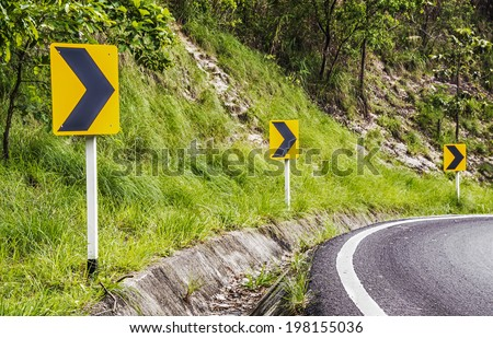 Road Signs warn drivers for ahead dangerous curve on down hill.  - stock photo