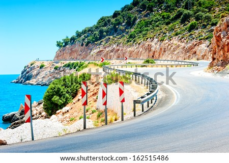 Road signs warn of the dangerous turn in the mountains - stock photo