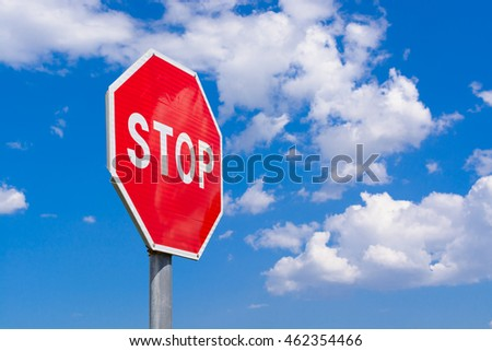 Road stop sign on a background of clouds
