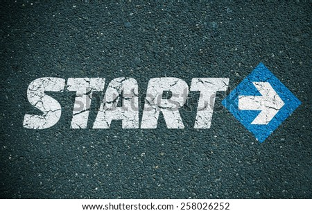 Road surface with the word start written on it and an arrow - stock photo