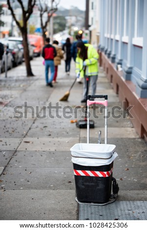 Road sweeper worker cleaning footpath  with broom tool in USA