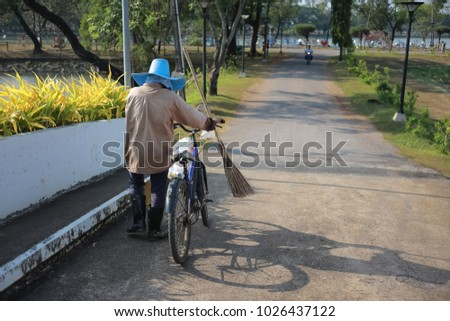 road sweeper worker with wooden broom tool pushing bicycle into a public park