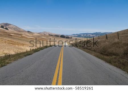 Road through dry brown hills, Los Osos, California - stock photo