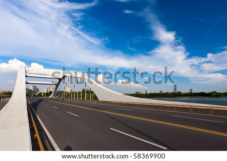 road through the bridge with blue sky background of a city. - stock photo