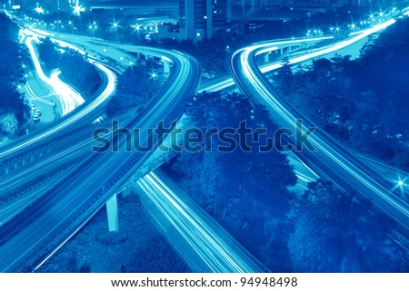 road through the bridge with blue sky background of a city - stock photo