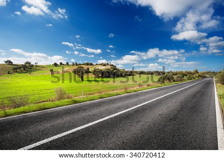 Road through the green field of Sardinia countryside in sunny day - stock photo
