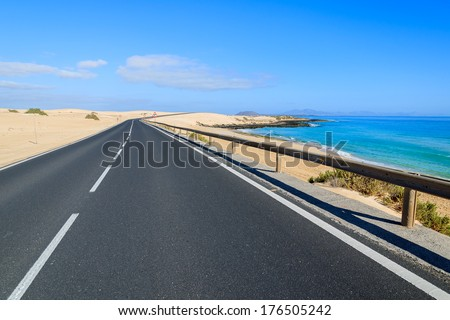 Road to Corralejo with sand dunes along and ocean water view, Fuerteventura, Canary Islands, Spain - stock photo