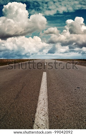 Road to nowhere. Clouds over highway road that stretches to infinity - stock photo