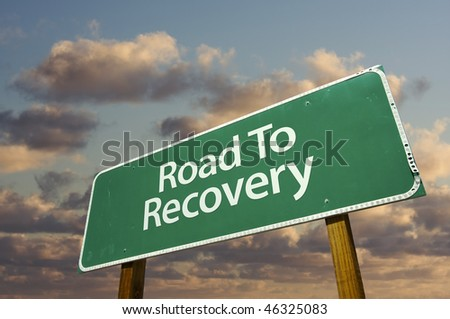 Road To Recovery Green Road Sign with dramatic clouds and sky. - stock photo