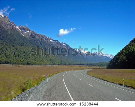 Road to Somewhere.  A New Zealand road disappearing into the distance backed by a snow capped South Island mountain range. - stock photo