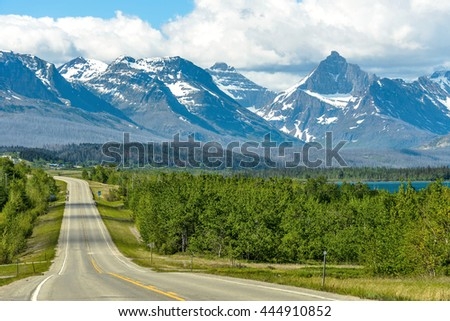 Road to the Mountains - A cloudy spring morning view of a winding road (U.S. 89) extending towards snow-capped high mountain peaks in Glacier National Park, Montana, USA.