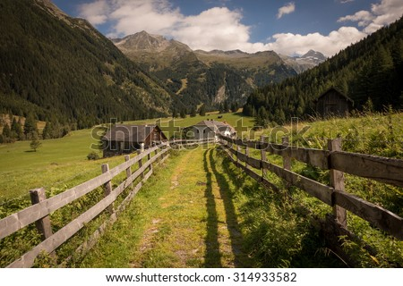 Road towards Farmhouses with Fences and Mountains in the Background in Summer, Mallnitz, High Tauern, Alps, Austria, Europe - stock photo