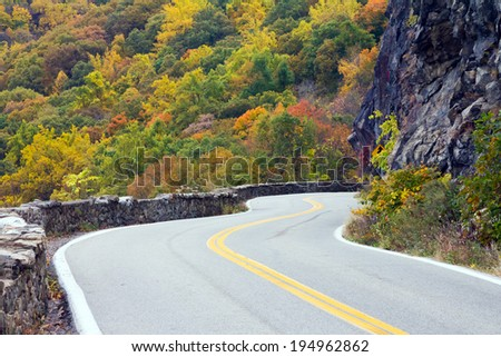 Road travels through a colorful fall forest in New York - stock photo