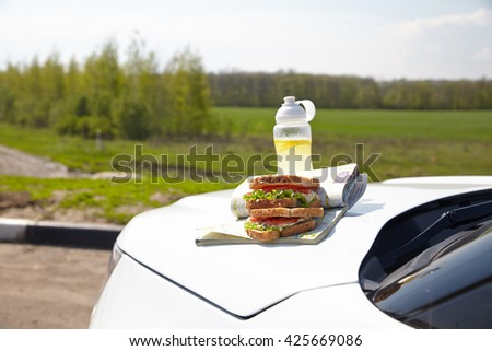 Road trip breakfast on a car hood - sandwiches and lemonade - stock photo