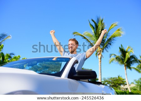 Road trip travel - free man driving car in freedom. Happy young adult cheering in convertible for his summer vacations - stock photo