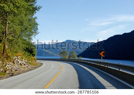 Road turning left around fiord, Norway - stock photo