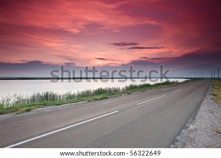 road under dramatic red sunset sky - stock photo