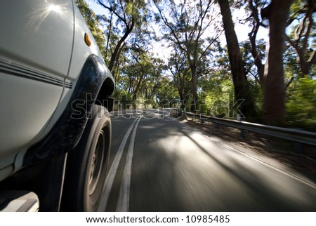 Road view of vehicle speeding by on country road - stock photo