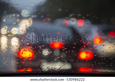 Road view through car window with rain drops. Blurred picture.