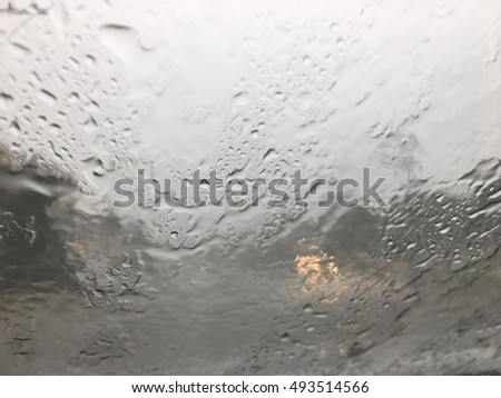Road view through car window with rain drops, Driving in a heavy rain. A traffic in the heavy rain,View through the window and Shallow depth of field composition.