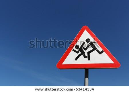 "Road warning sign ""Running Kids"" over blue sky - stock photo"