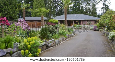 Road with brick house, rock wall and spring landscape.