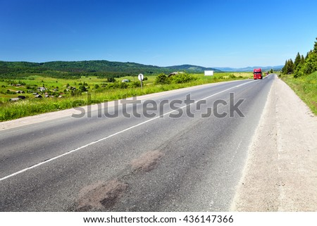 Road with cars on horizon. Rural landscape in summer day