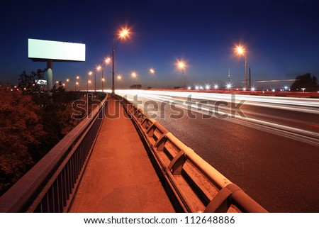 Road with lanterns and blank billboard at dark night in city. - stock photo