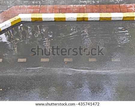 Road with water can't flows down on the bus lane. Flooding road is big problem in Bangkok on raining season that make car can't drive fast. This flood will make people hard to take bus back home. - stock photo