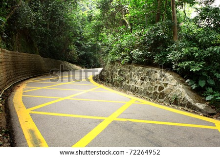 road with yellow lines and trees - stock photo