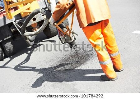Road worker at asphalt roadway street patching reaparing work