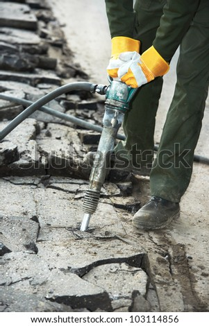 Road worker breaking street asphalt with jackhammer pneumatic paving breaker drill at repairing roadwork - stock photo