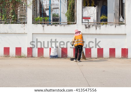 Road worker sweeper cleaning street with broom tool - stock photo
