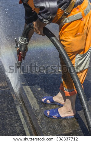 Road worker wearing slippers and using water jet to remove detritus from tram tracks