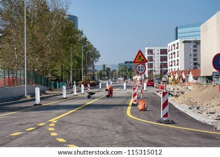 Road workers at the asphalt repairing works - stock photo