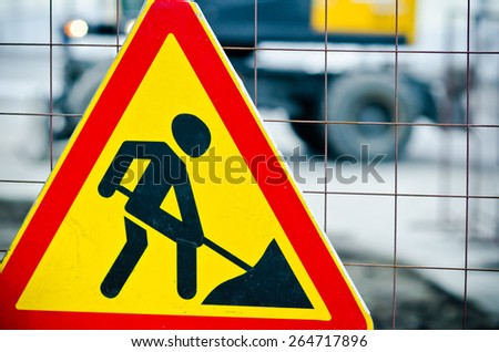 Road works sign hanging on a fence close up - stock photo