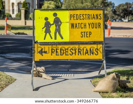Road works sign warning pedestrians to watch their step and walk to the left on the footpath.