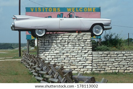 Roadside attraction of a pink Cadillac convertible on a fence, East TX - stock photo