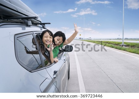 Roadtrip concept: Portrait of two happy children waving hands on the camera while sticking their head out the car window - stock photo