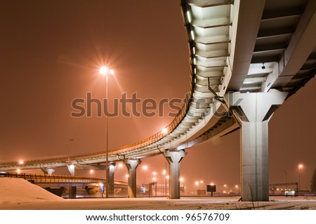 Roadway at night, sky is colored in orange - stock photo