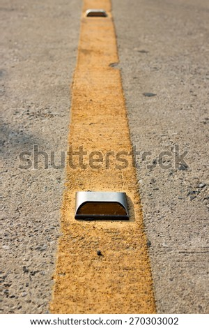 Roadway divider yellow line and marker - stock photo