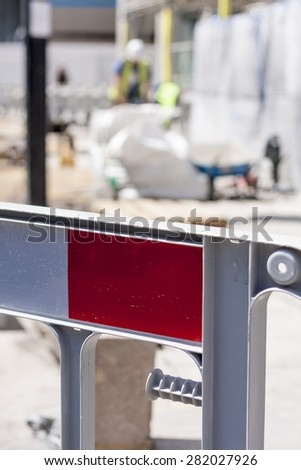 Roadworks barrier with construction worker out of focus in background - stock photo
