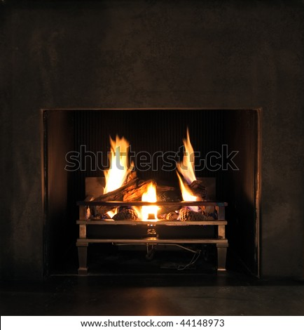 Roaring flames in a modern fireplace with shiny slate framing. Space for your text.