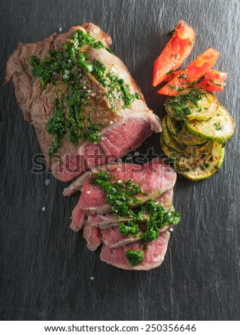 Roast Beef dinner with roasted zucchini, pepper and salsa verde on a stone plate - stock photo