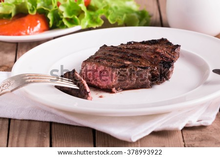 Roast Beef Fillet served on white plate with cutlery.  - stock photo