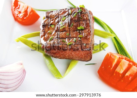 roast beef meat fillet entrecote served with tomato on white plate isolated over white background - stock photo