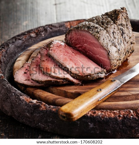 Roast beef on cutting board and knife - stock photo