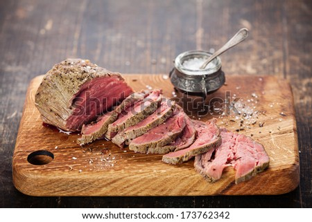 Roast beef on cutting board and saltcellar  - stock photo