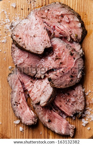 Roast beef on cutting board with salt and pepper - stock photo